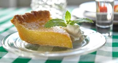 A slice of Maysville transparent pie sits on a glass plate atop a green-and-white checked tablecloth
