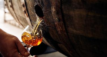 Bourbon flows from a barrel into a tasting glass
