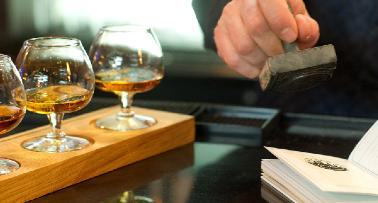 A man stamps a passport book on a Kentucky bourbon trail, with a row of tasting glasses beside him