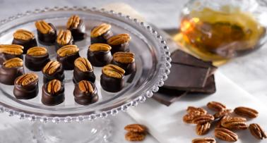 A cake stand filled with bourbon balls, with more chocolate and nuts scattered on the tabletop below
