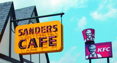 A yellow sign marks the entrance of Sanders Cafe, home of the original Kentucky Fried Chicken