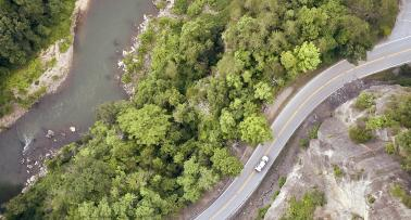 Overhead shot of a car driving a winding road along a river in Kentucky