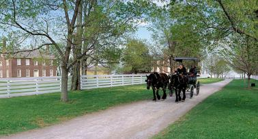 A horse-drawn carriage travels a gravel road at Shaker Village of Pleasant Hill in Harrodsburg, KY
