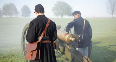 Two Civil War reenactors fire a cannon at Camp Nelson