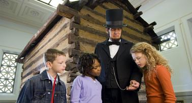 A costumed Abraham Lincoln reenactor stands in front of his replica birth cabin with a group of children