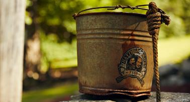 Close up of a rusty bucket bearing a Hatfield & McCoy logo