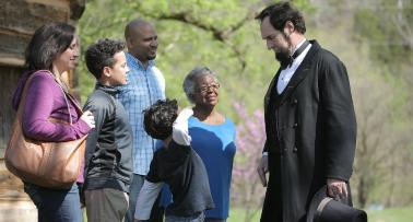 A costumed Abraham Lincoln reenactor interacts with a multigenerational family