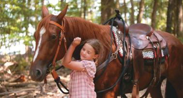 A young girl hugs a brown horse around its neck