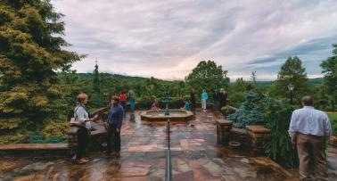 People mingle on a stone overlook at Baker Arboretum in Kentucky