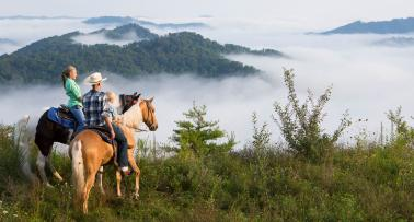 A family on horseback looks out at a misty mountain landscape in Kentucky