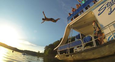 A man dives off a houseboat into a lake in Kentucky