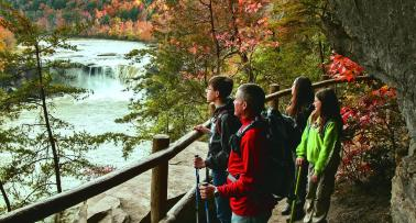 A family looks out at Cumberland Falls from a scenic overlook