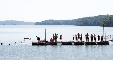 A group of boys hang out on a pier on Kentucky Lake, with a few diving off the end