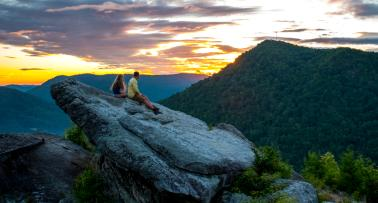 Two people sit on top of a rock in the middle of a mountain landscape on Pine Mountain in Kentucky