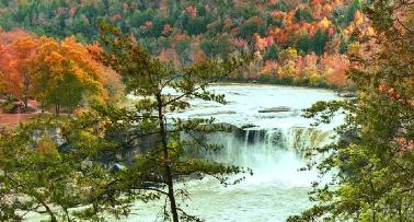 A wide shot of Kentucky's Cumberland Falls, surrounded by fall foliage