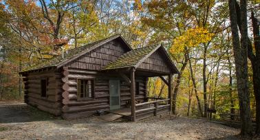 A log cabin sits in a fall forest at Pine Mountain State Resort Park