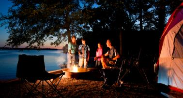 A family huddles around a campfire at a Kentucky campground at night