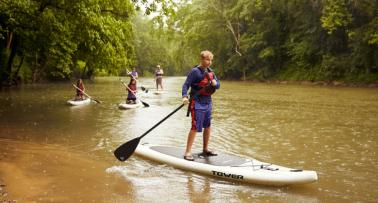 A family paddleboards on a Kentucky waterway
