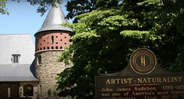 Exterior of the John James Audubon State Park Museum & Nature Center with a historical marker in the foreground