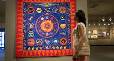 Woman looking at brightly colored quilt at the National Quilt Museum in Paducah, Kentucky