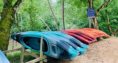 Blue and Red Kayaks on rack for rent