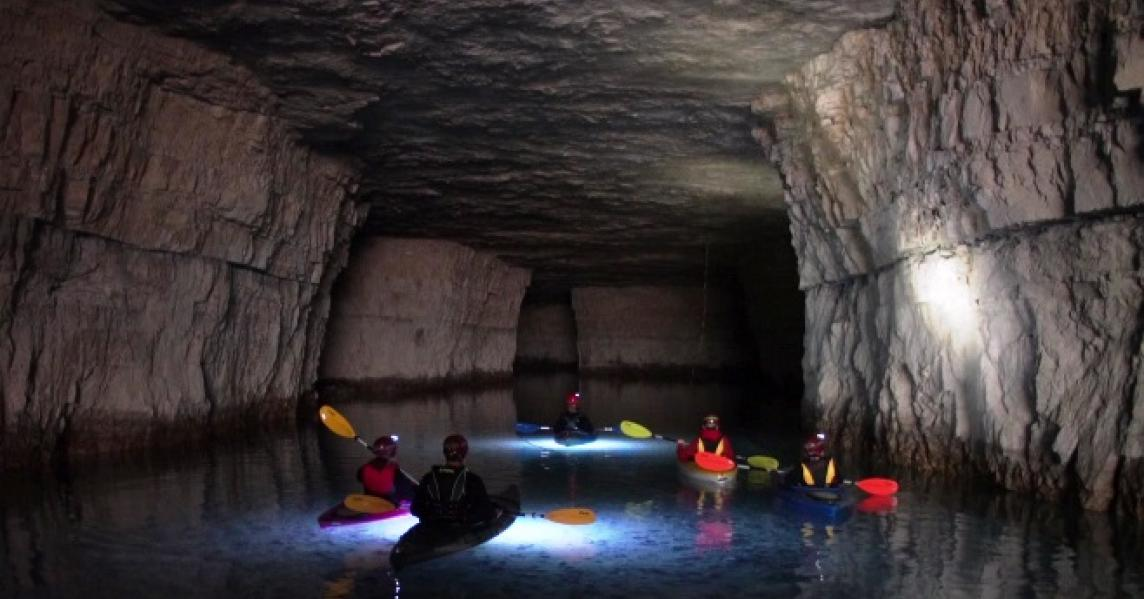 Kayakers navigate a natural tunnel at Red River Gorge in Kentucky