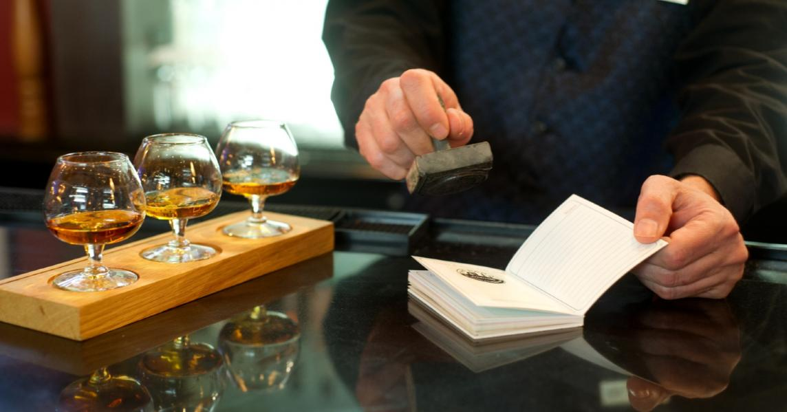 A bartender stamps a passport on the Urban Bourbon Trail in Louisville, KY