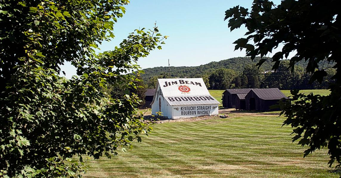 The white barn at Jim Beam Distillery is pictured in the middle of a lush green field