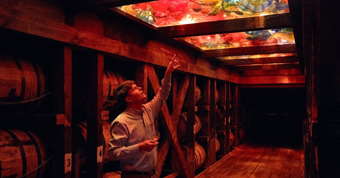 A man looks up at the colorful Chihuly ceiling at Maker's Mark Distillery