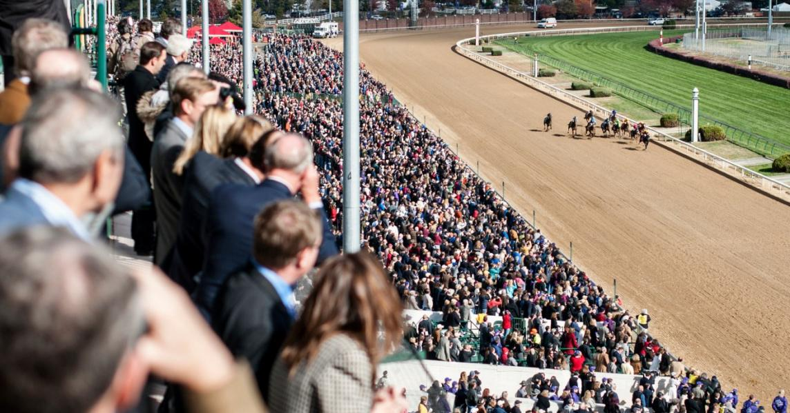 A crowd watches horses run the Kentucky Derby at Churchill Downs