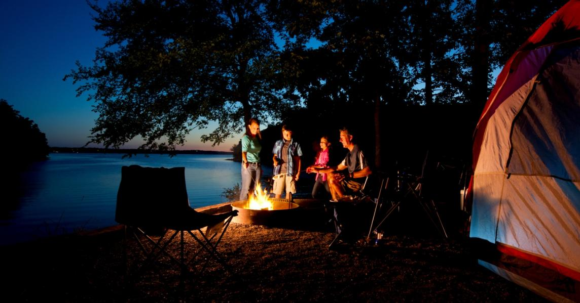 A family gathers around a fire at a lakefront campground in Kentucky