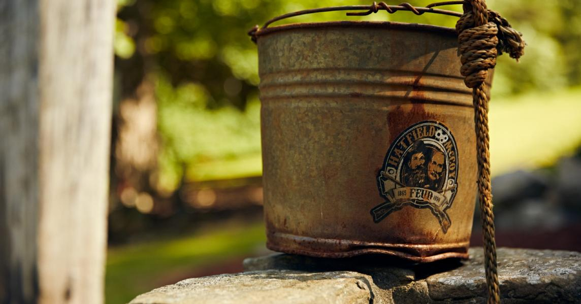 A vintage bucket emblazoned with a Hatfield & McCoy logo