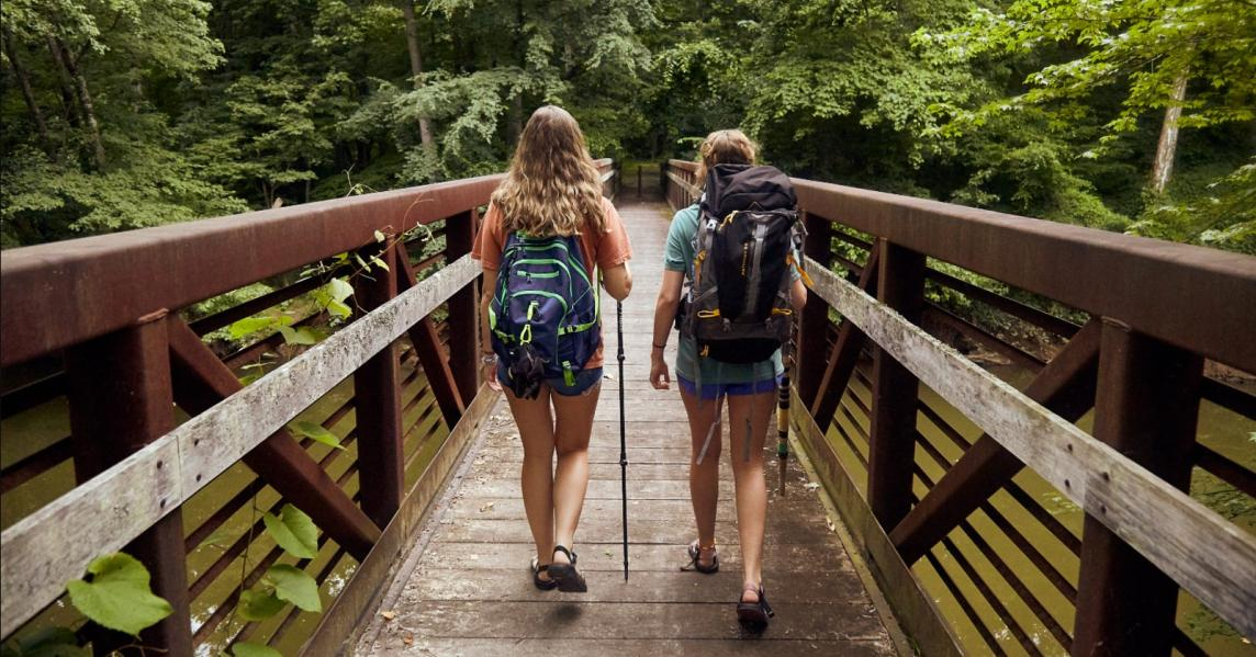 Two women hike over a wooden bridge in the Kentucky Trail Town of Dawson Springs