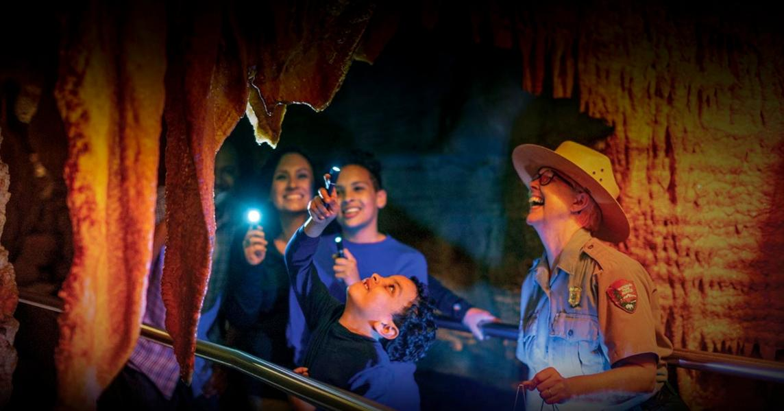 A family explores Mammoth Cave by flashlight
