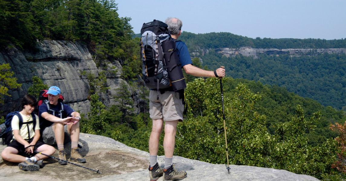 A hiker stands atop a rocky vista at Red River Gorge