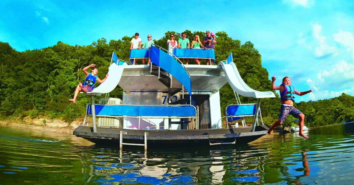 Kids slide down water slides on a houseboat in Lake Cumberland