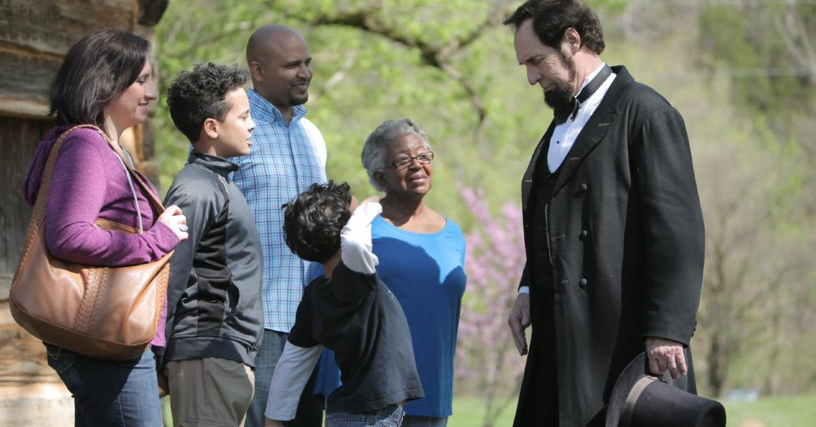 An Abraham Lincoln reenactor engages with a family at a Kentucky historic site
