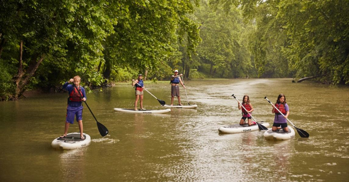 A family paddleboards on a Kentucky river