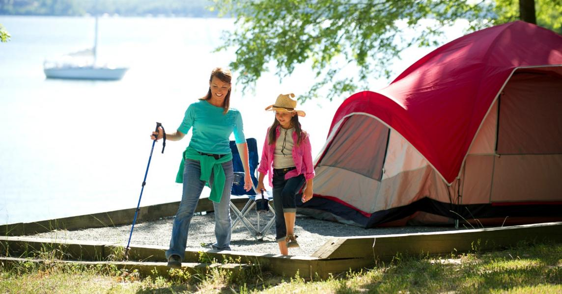 A woman and daughter camp by a lake at the Land Between the Lakes