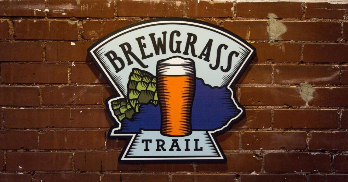 A sign for Kentucky's Brewgrass Trail hangs on a brick wall