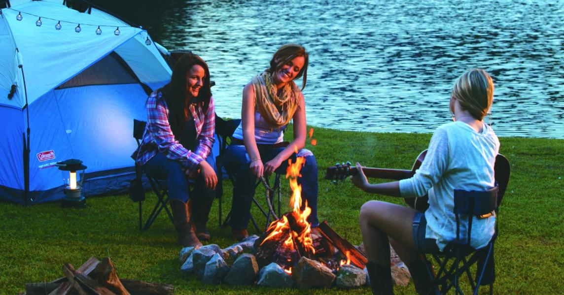 Women hang out and play guitar around a campfire at a lakefront Kentucky campground