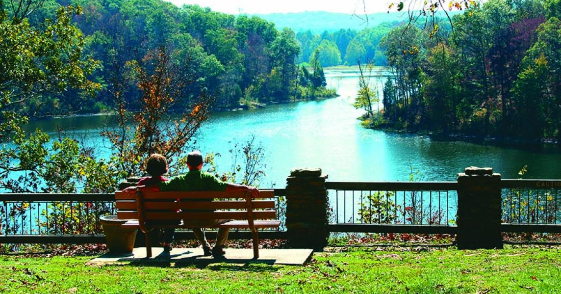 couple sitting on bench looking at lake