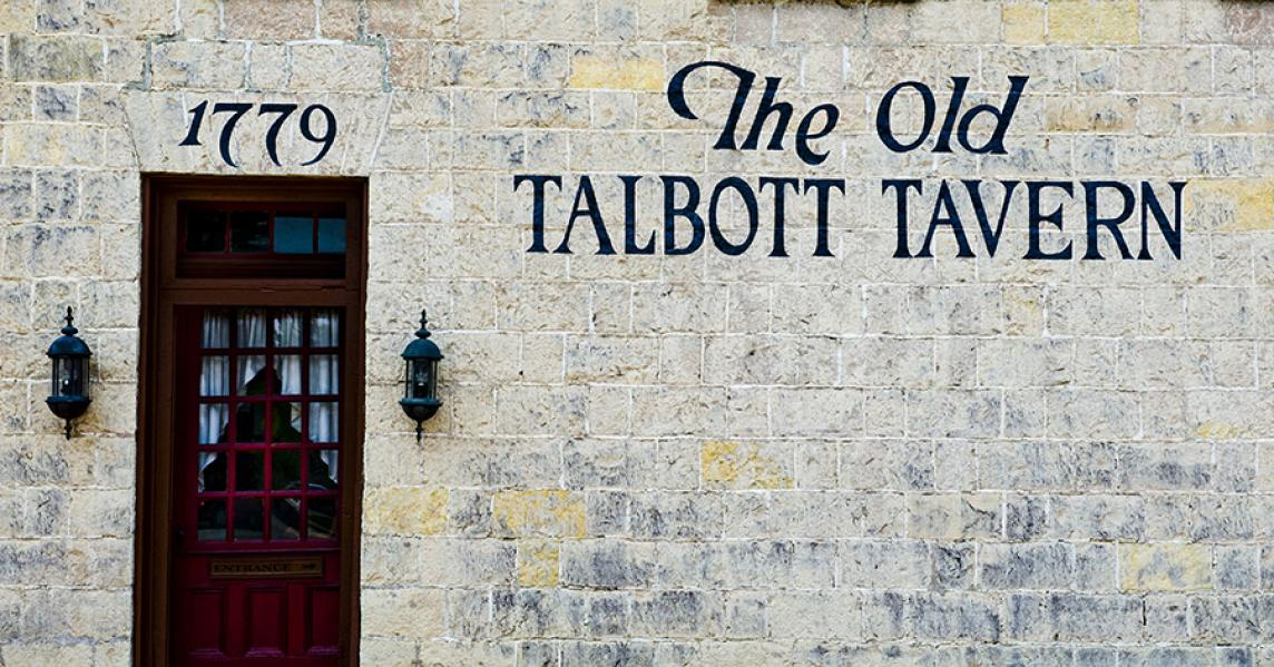 Outside The Old Talbot Tavern. Rock building. Brown door to entrance.