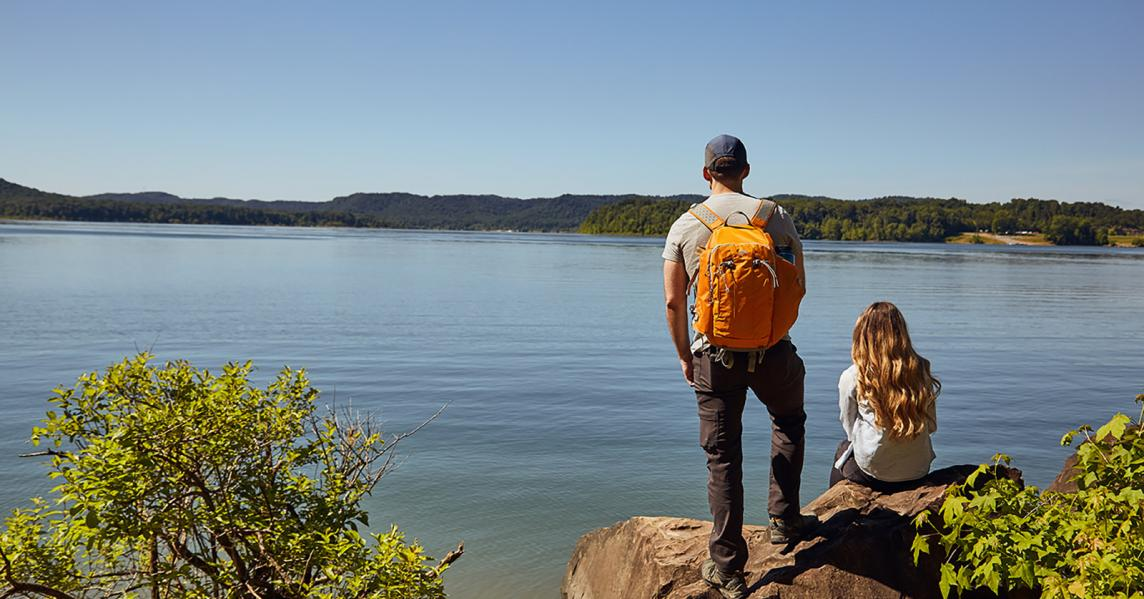 guy with back pack on with girl sitting on rock in morehead