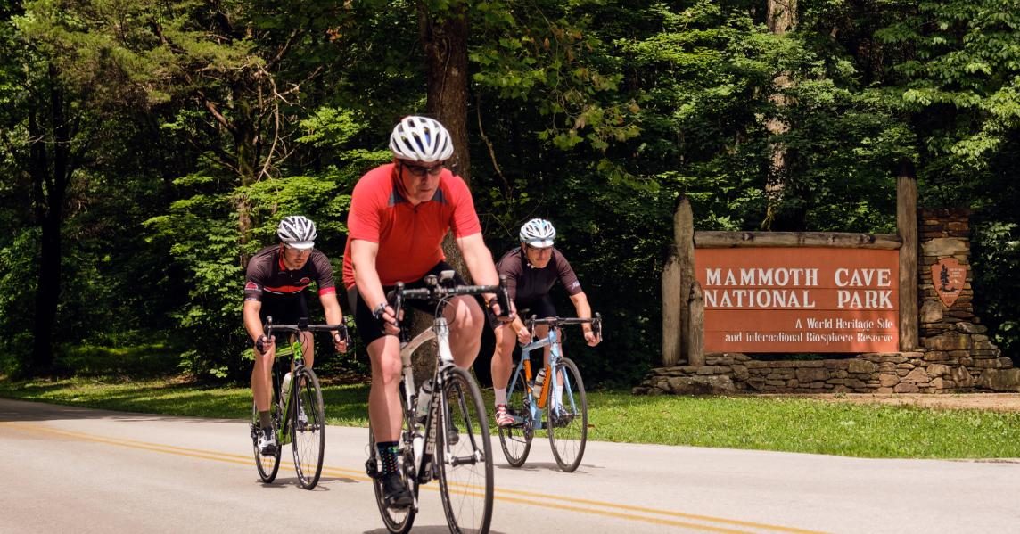 men biking in front of mammoth cave sign