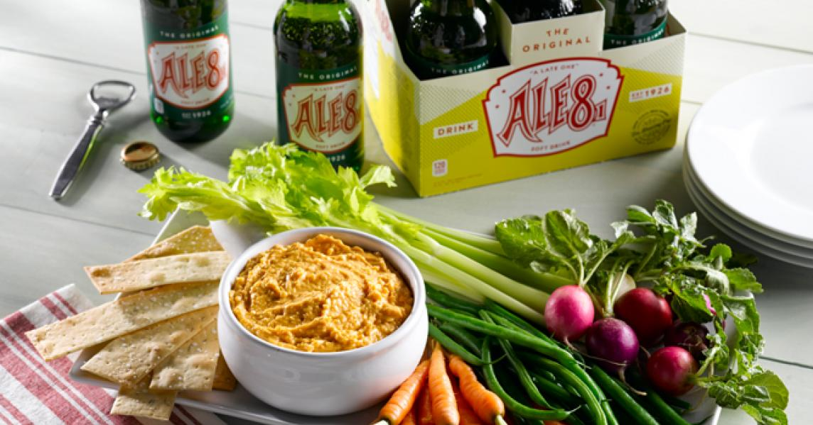 A bowl of Kentucky beer cheese is surrounded by fresh veggies for dipping and a six-pack of Ale-8-One soda
