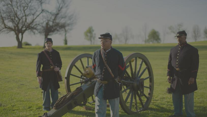 An African American man dressed in a Civil War-era uniform stands before a cannon during a reenactment