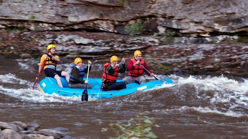 A group of people navigate rapids on a Kentucky whitewater rafting trip