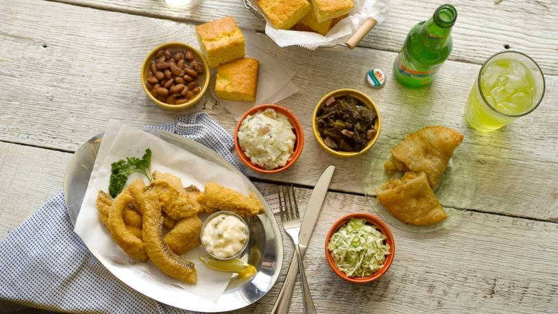 An overhead shot of a wooden table set with traditional foods of the Southern Shorelines region of Kentucky, including fried fish and Ski soda