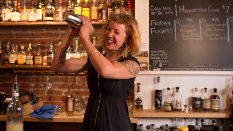 A female bartender shakes a cocktail at a bourbon bar on the B-Line in Northern Kentucky